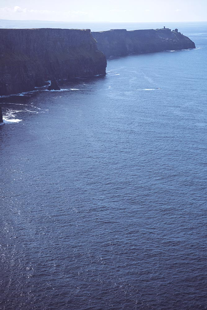 Massive cliffs of Moher on Atlantic ocean on sunny day, Ireland