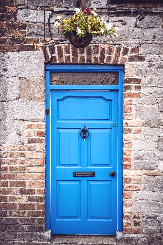 Bright blue door in brick wall of English house.
