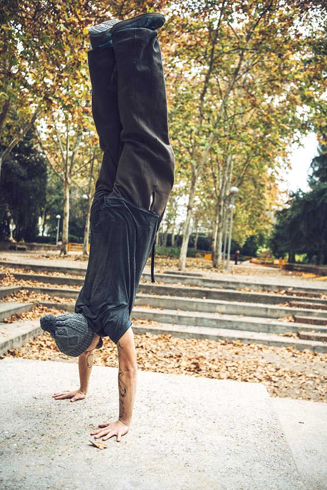 Sportive man doing handstand in park