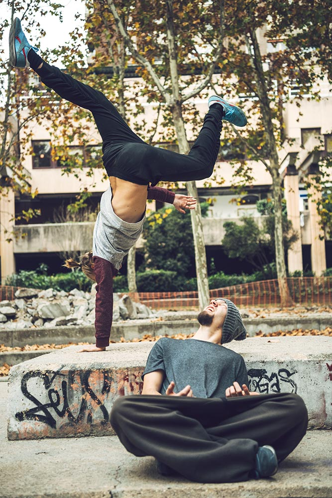 Playful friends training parkour in park