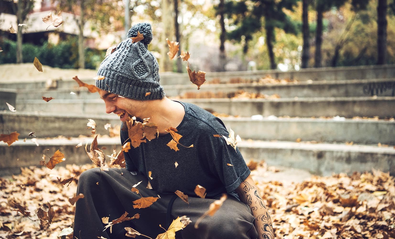 Laughing sportive man in leaves