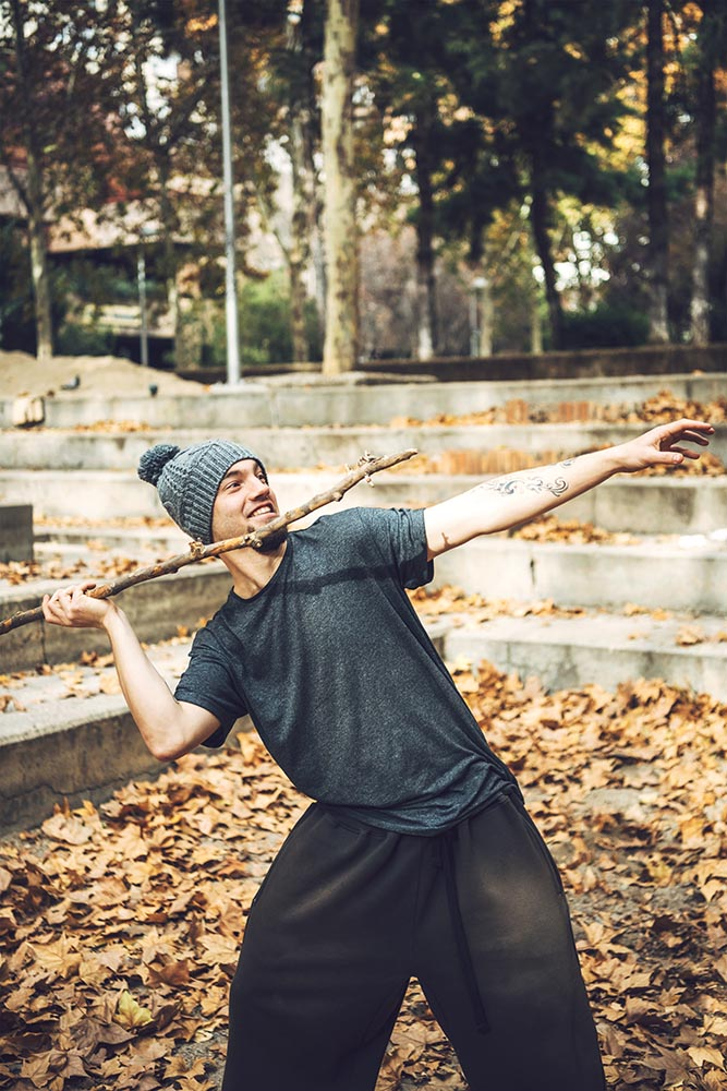 Playful parkour athlete throwing stick