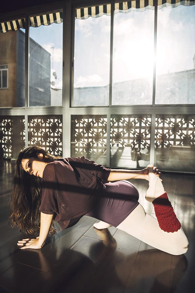 Confident woman stretching in sunlight