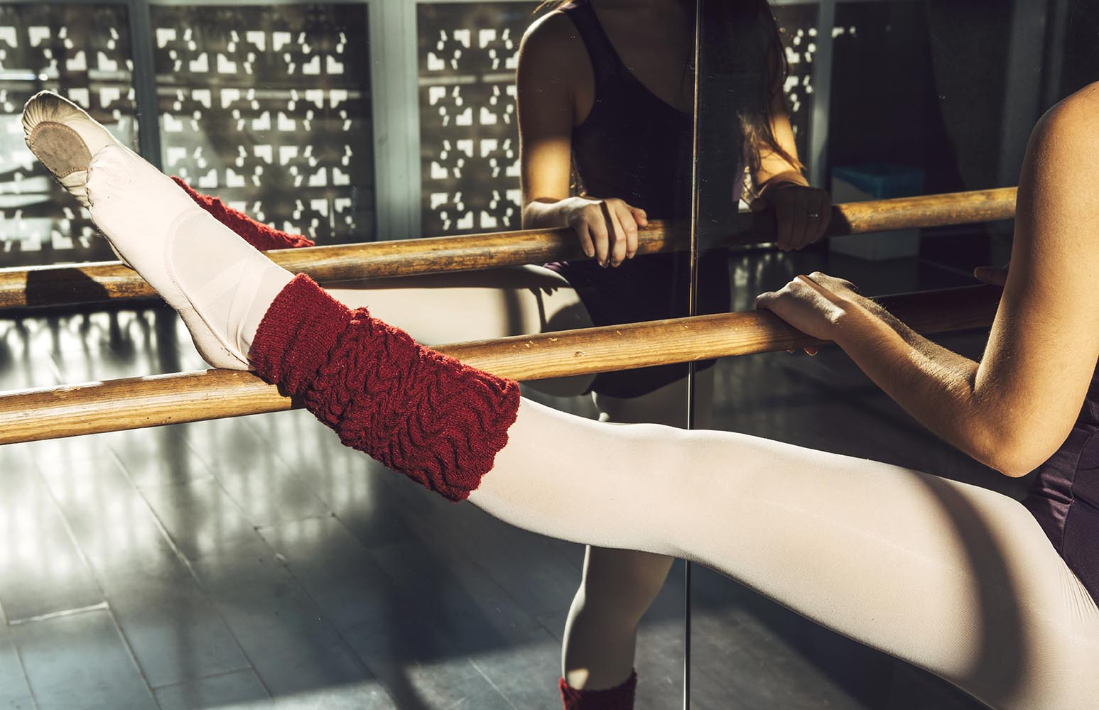 Crop woman stretching with barre