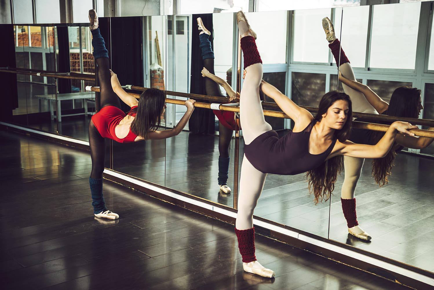 Ballerinas stretching with barre