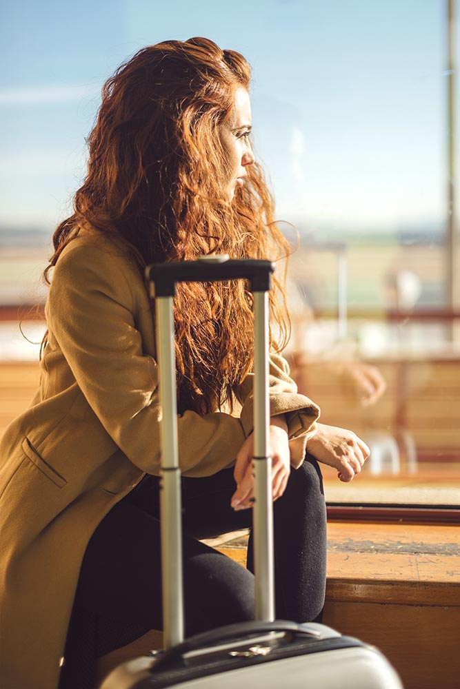 Woman with suitcase sitting in airport