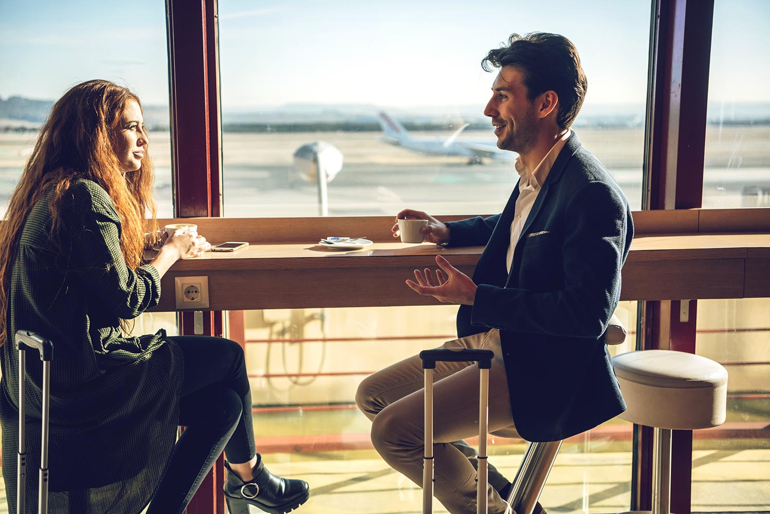 Happy couple sitting in airport cafe