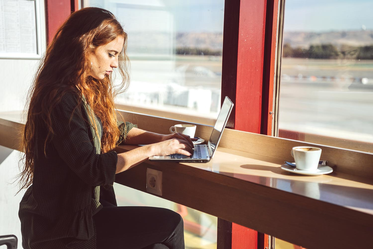 Woman with laptop in airport cafe