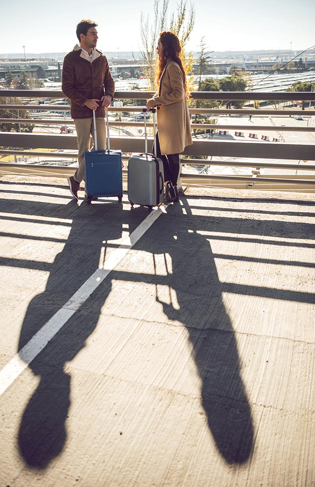 Couple with suitcases standing at handrail