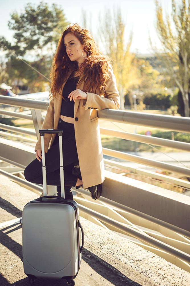 Confident woman with luggage outside