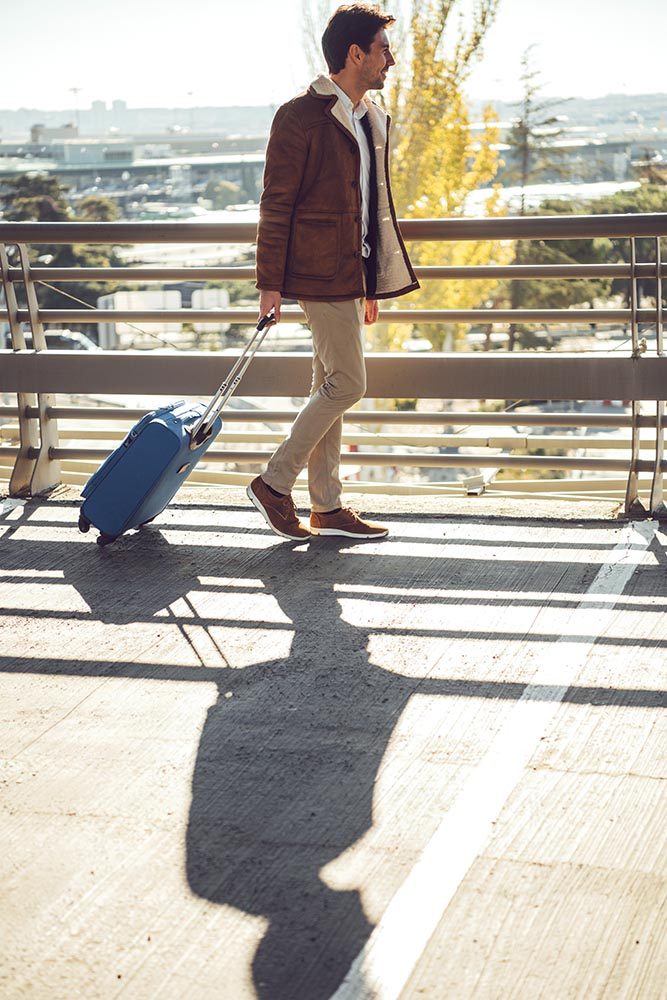 Elegant man with suitcase in airport