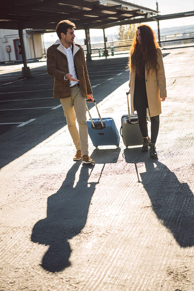 Stylish couple with baggage walking
