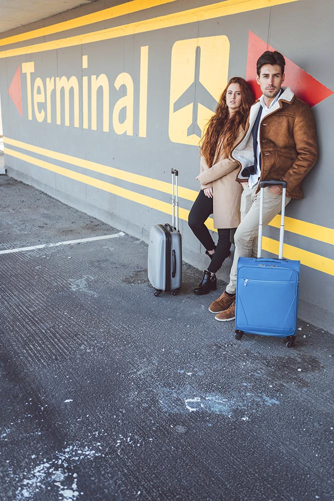 Couple with suitcases leaning on terminal wall