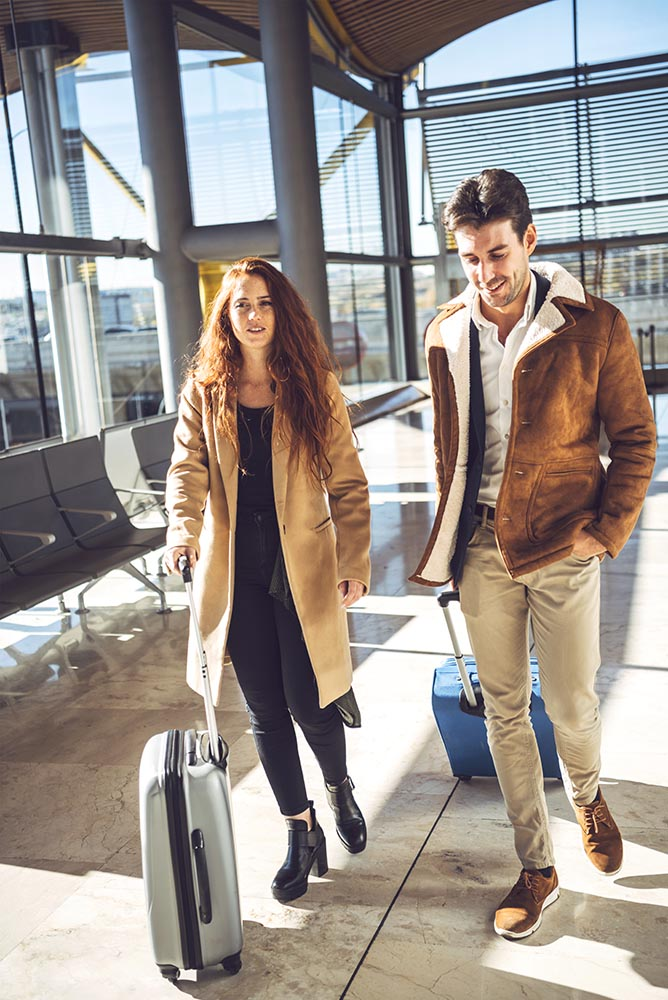 Cheerful happy couple walking in terminal