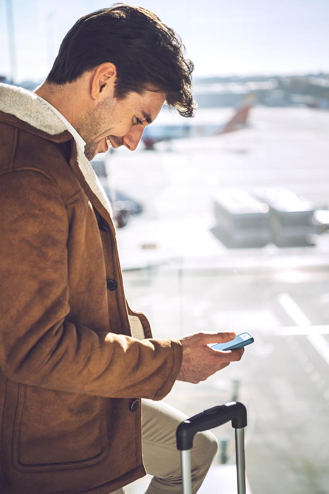 Cheerful man with smartphone in airport