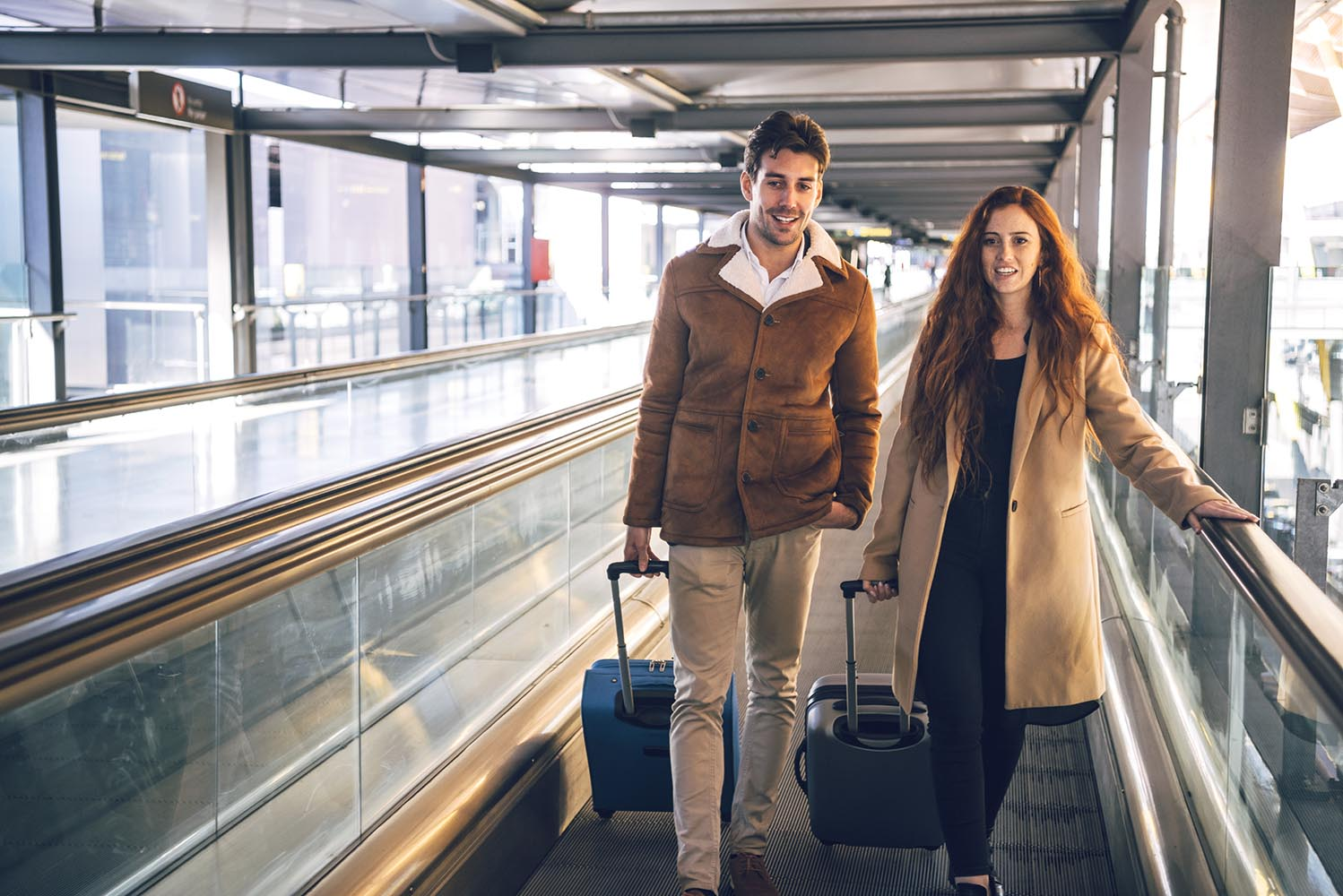 Cheerful couple with luggage on travelator