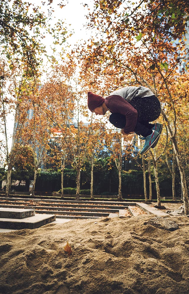Man jumping above sand pile in park