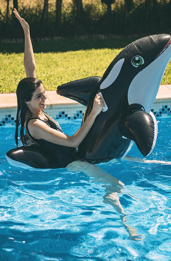 Excited young woman having fun in pool with inflatable fish toy