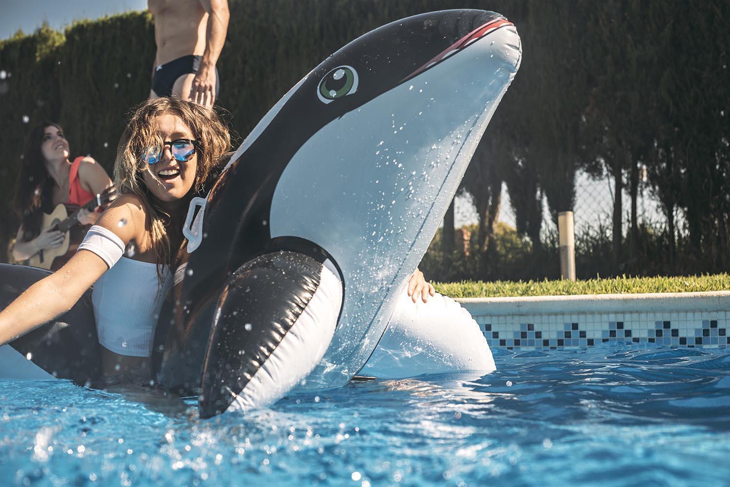 Girl floating over an inflatable orca whale