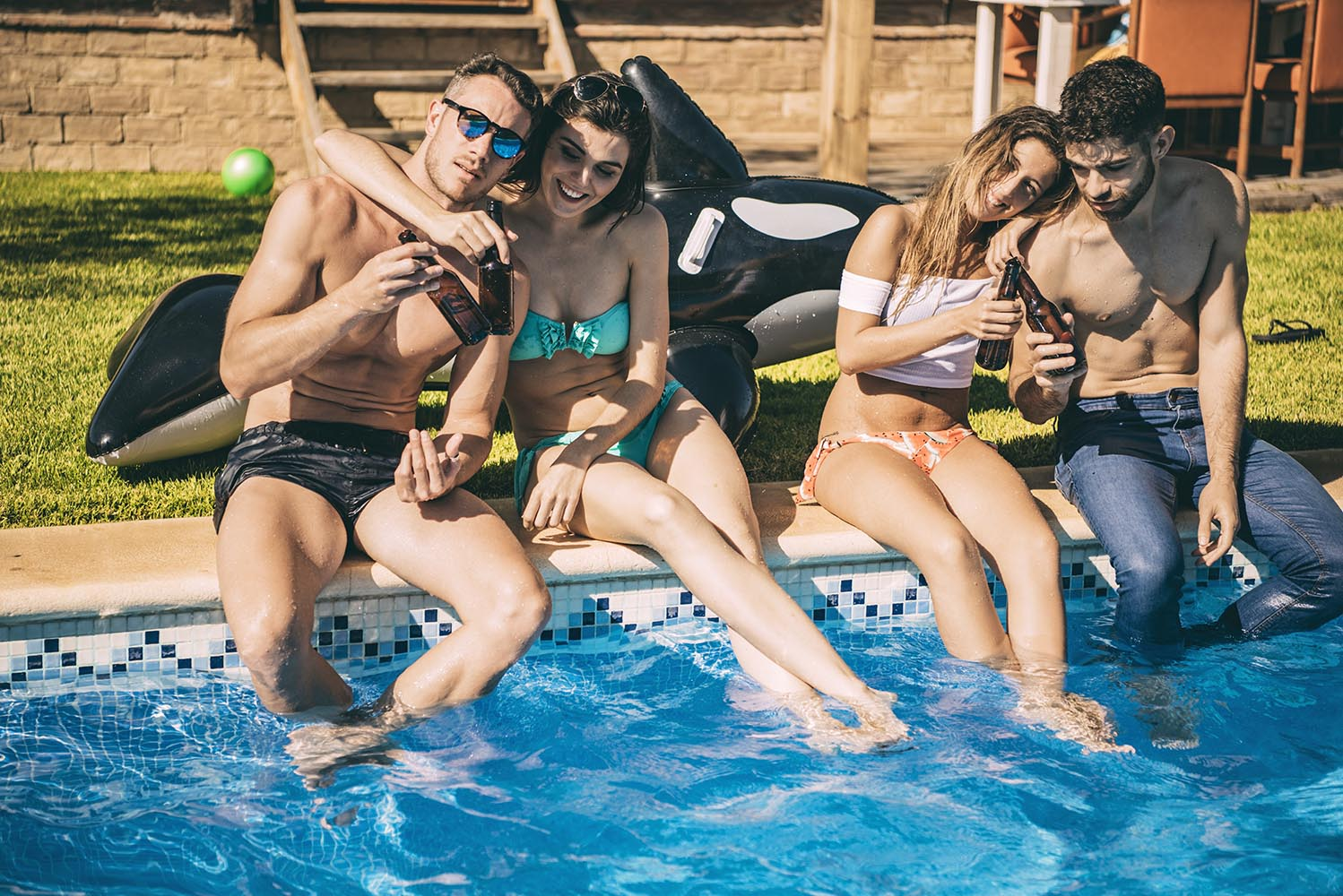 Young friends having drinks in pool