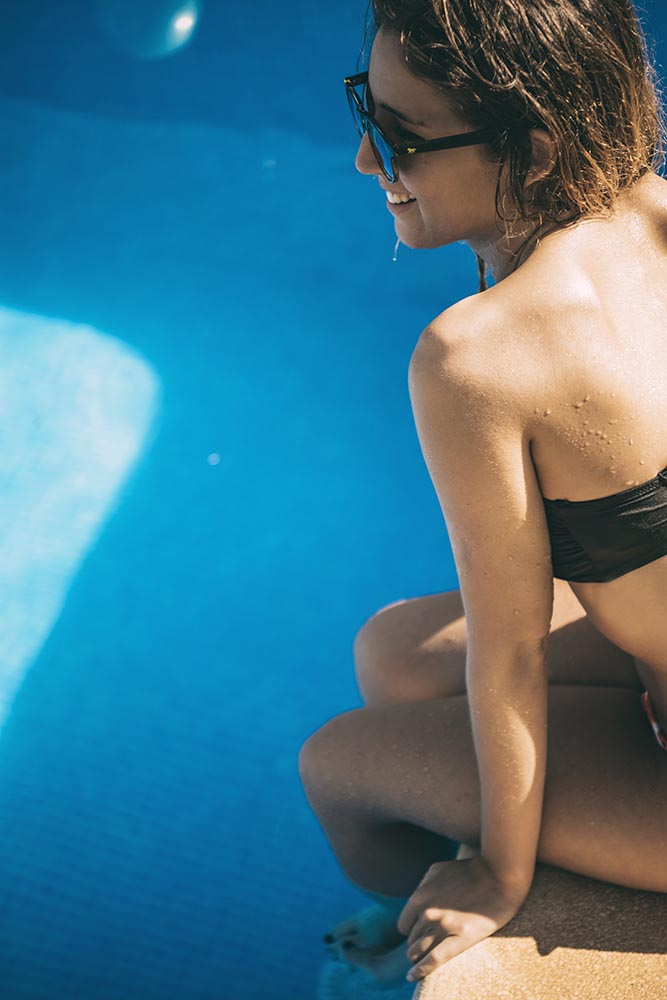 Girl in sunglasses sitting at swimming pool