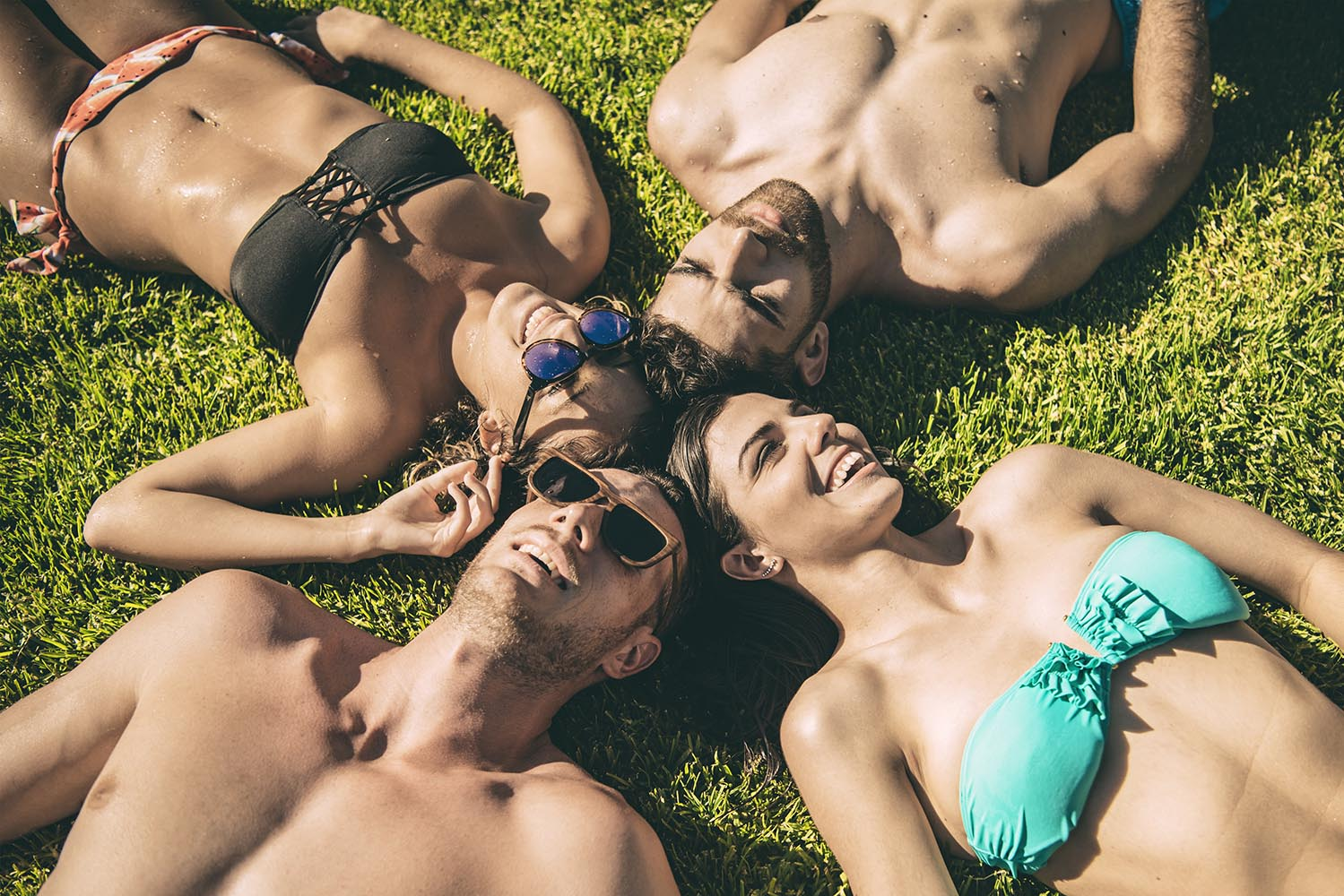 Friends lying on grass looking at sky