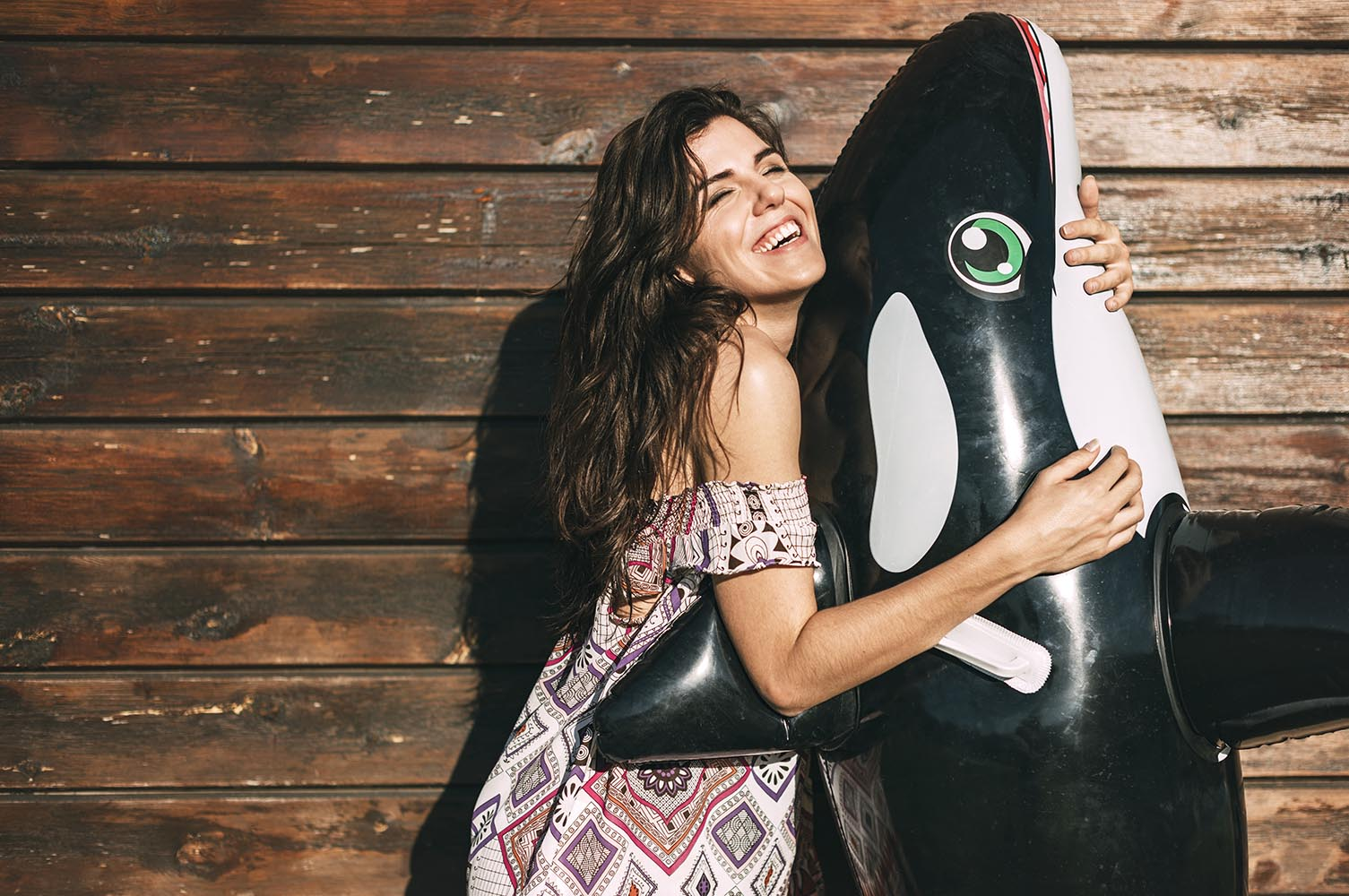 Beautiful young girl hugging an inflatable orca whale