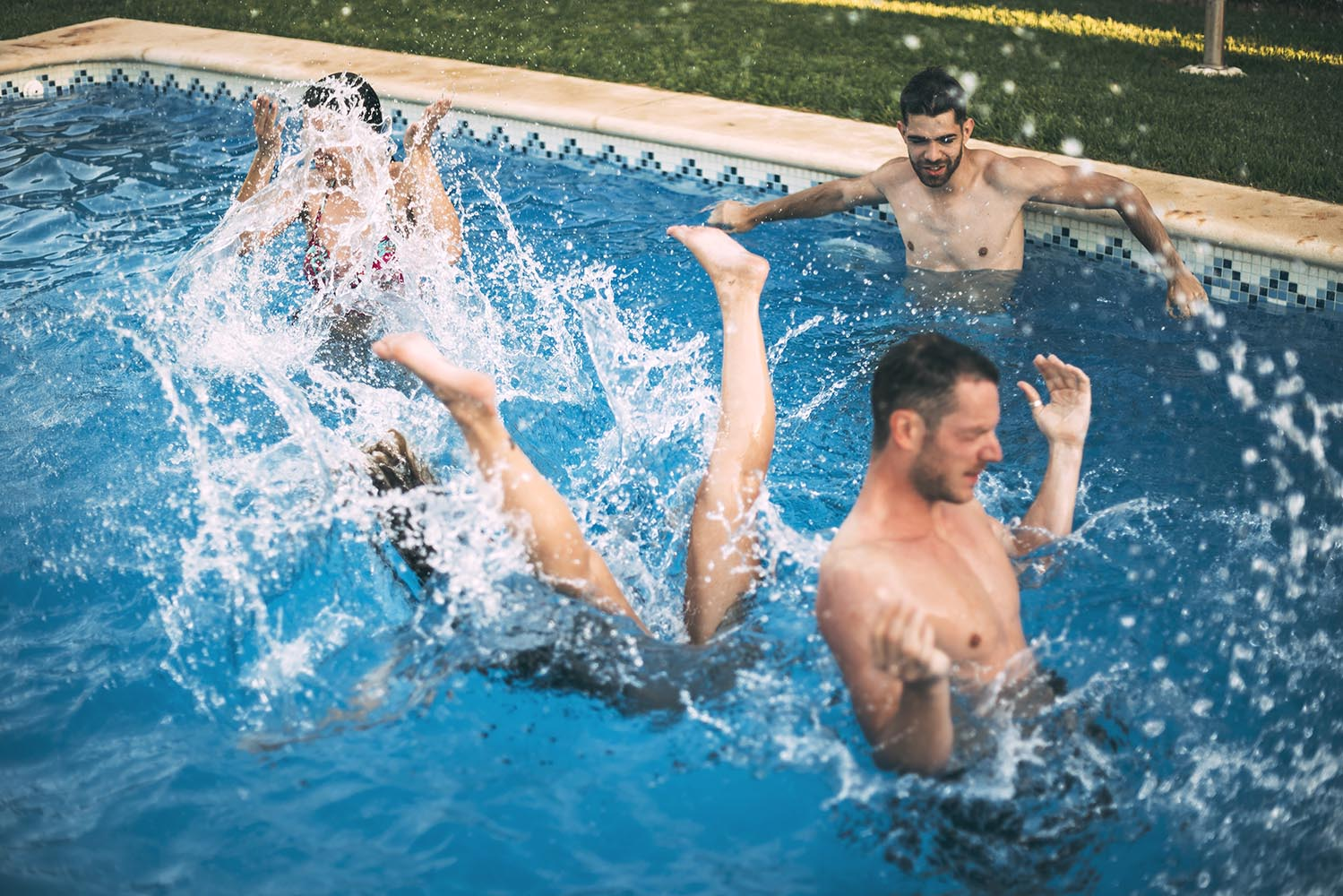 Friends jumping in pool and swimming