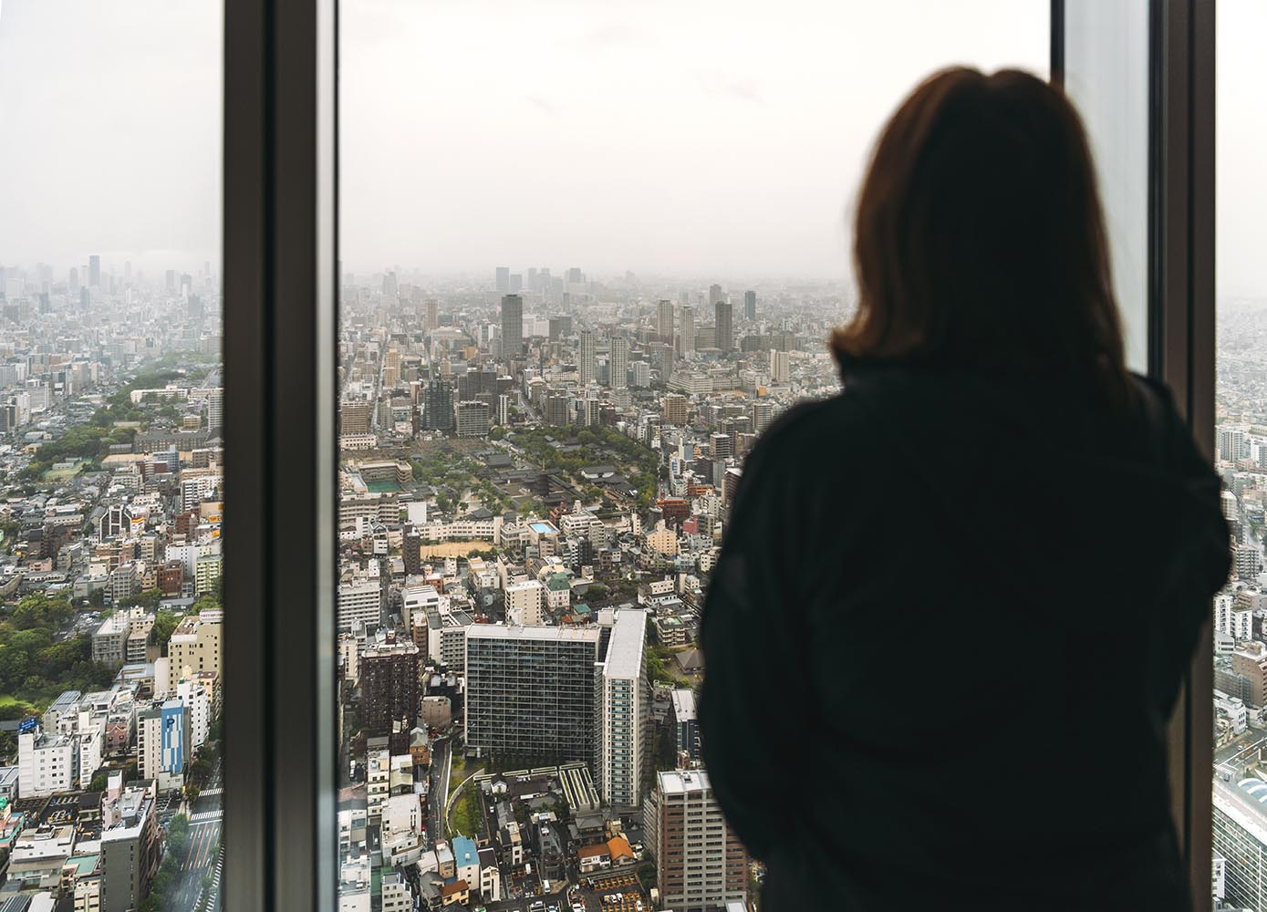 woman looking out the window in a skycrapper in Osaka city, Japa
